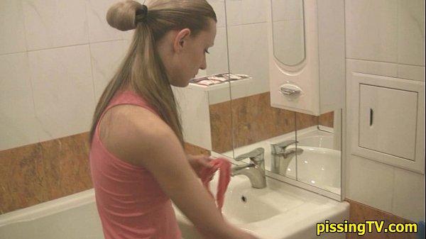 Женщина писает на унитазе в туалете